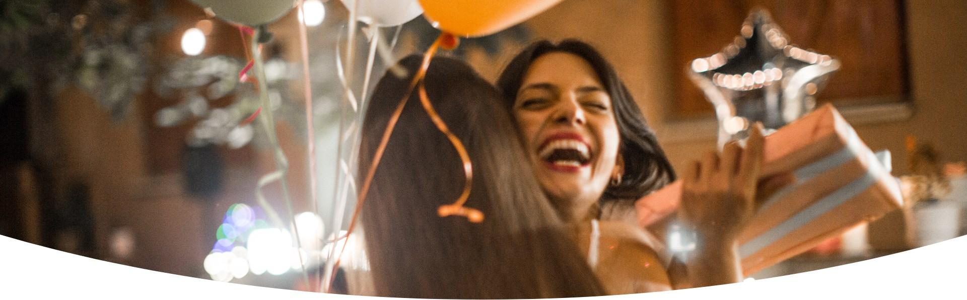 Due donne si abbracciano. Una delle due donne tiene in mano un regalo ed un palloncino e ride.