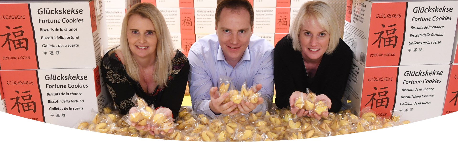 Alexandra, Christoph and Viktoria Brauch surrounded by fortune cookies.