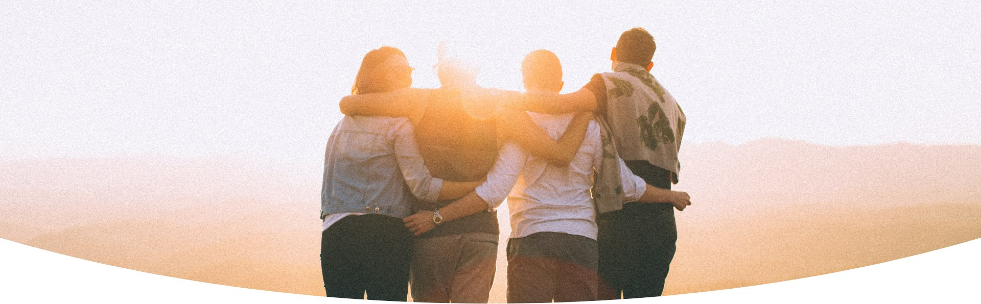 4 people hug each other, seen from behind, standing, looking into the horizon