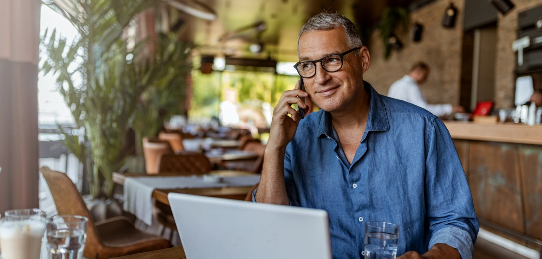 Man smiling in cafe with laptop and cell phone on ear