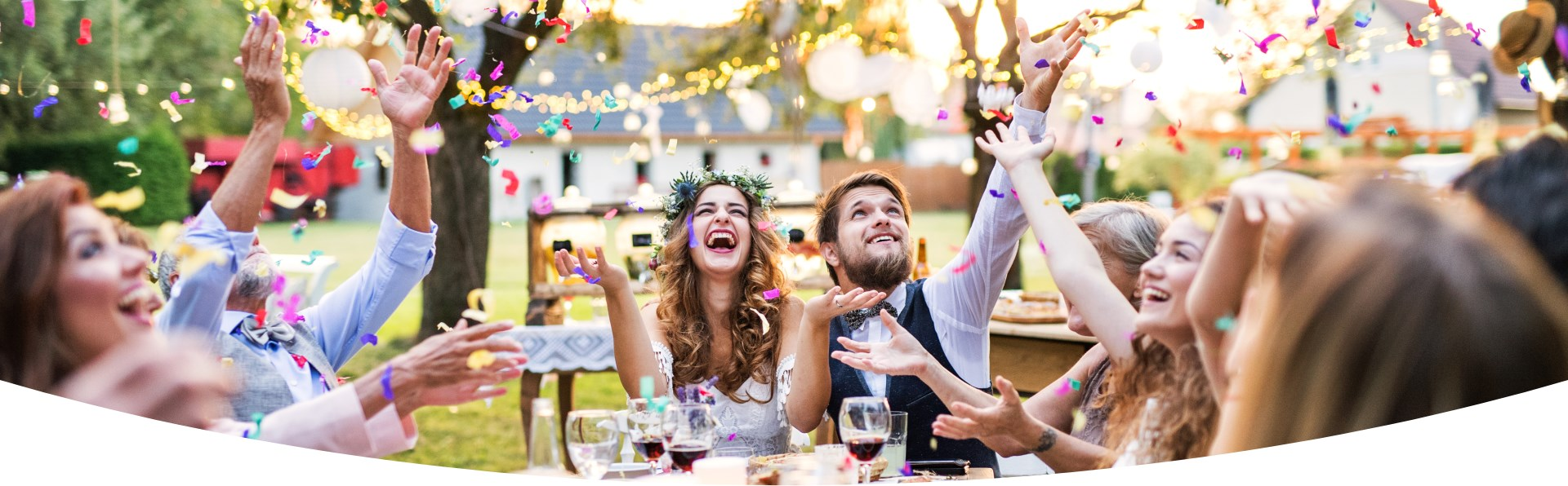 A wedding couple sit and celebrate happily with guests around an outdoor table. Confetti are thrown.